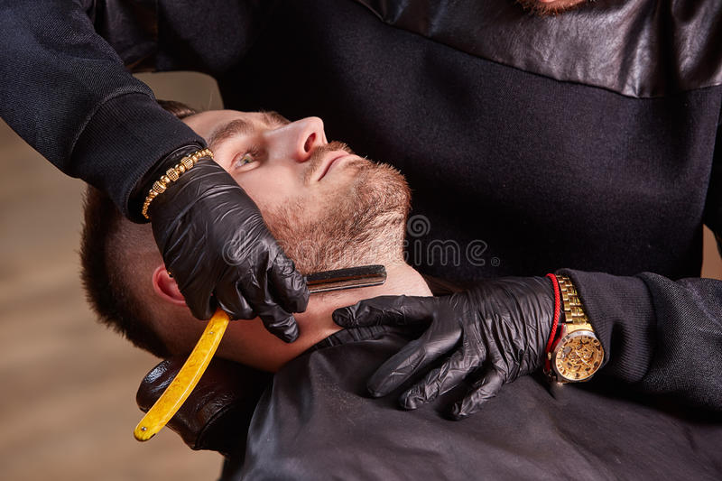 Master makes beards correction with shaver in barbershop salon. Close up photo. royalty free stock images