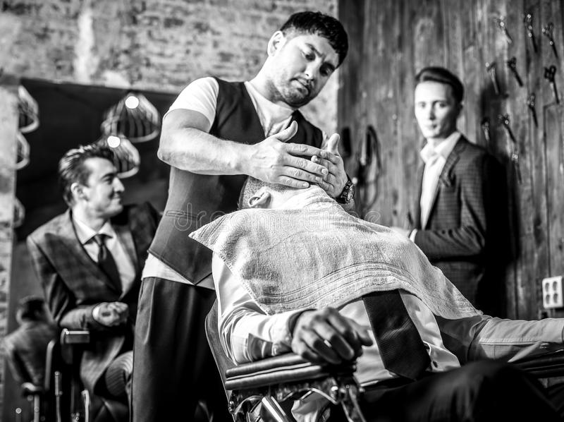 Master makes hair style in barbershop salon. Black-white close up photo. royalty free stock image