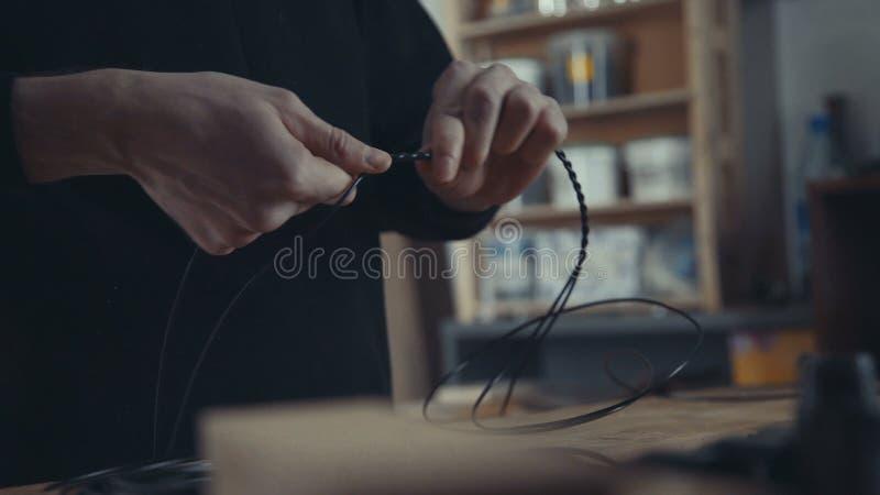 Master makes retro electrician black wire twists . Craft, loft royalty free stock photos