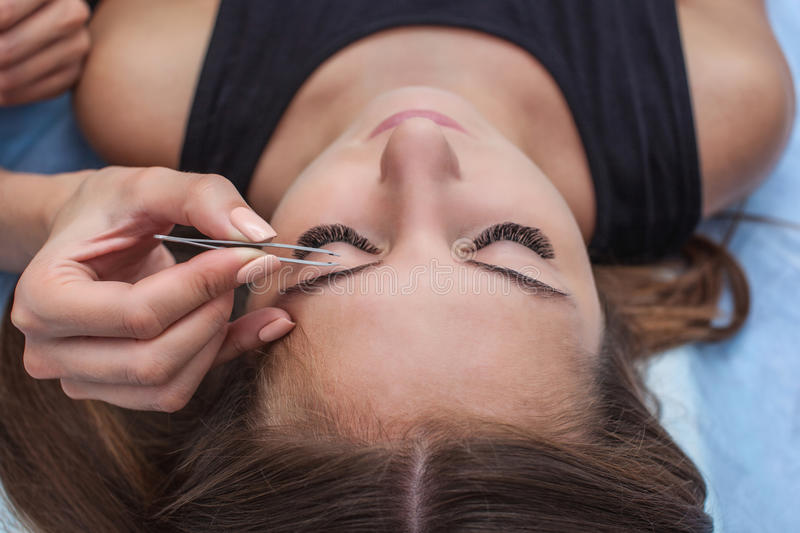 Master makeup corrects, and gives shape to pull out with forceps previously painted with henna eyebrows in a beauty salon. Professional care for face stock image