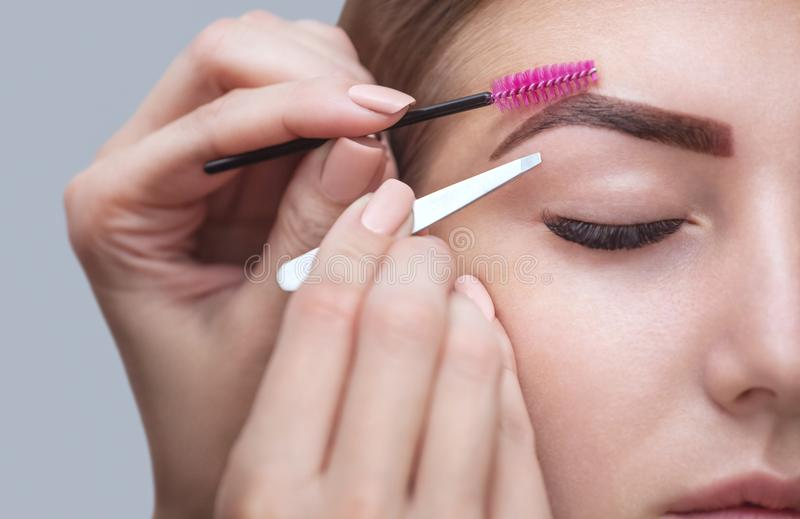 Master makeup corrects, and gives shape to pull out with forceps previously painted with henna eyebrows. In a beauty salon. Professional care for face royalty free stock image