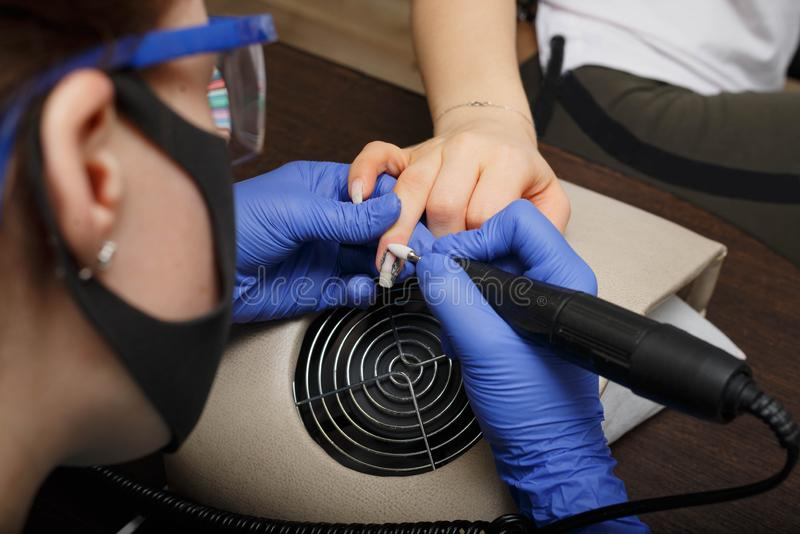 The master of nail service aligns the nails to the client with an electric machine. Creating a beautiful contour of the nail. The provision of nail services stock images