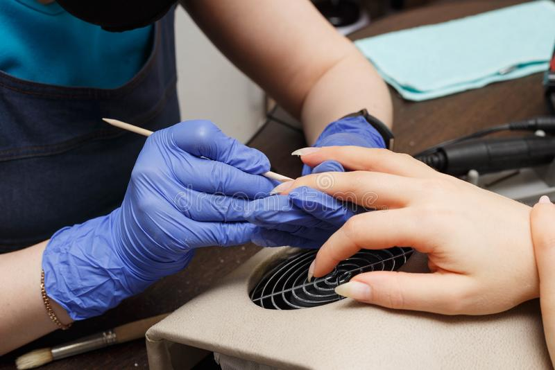 The master of nail service kills the cuticles. Rendering service in the cabin. Professional nail service stock photos
