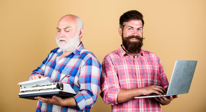 Master new technologies. Modern life and remnants of past. Senior man with typewriter and hipster with laptop. Battle of. Master new technologies. Modern life royalty free stock photography