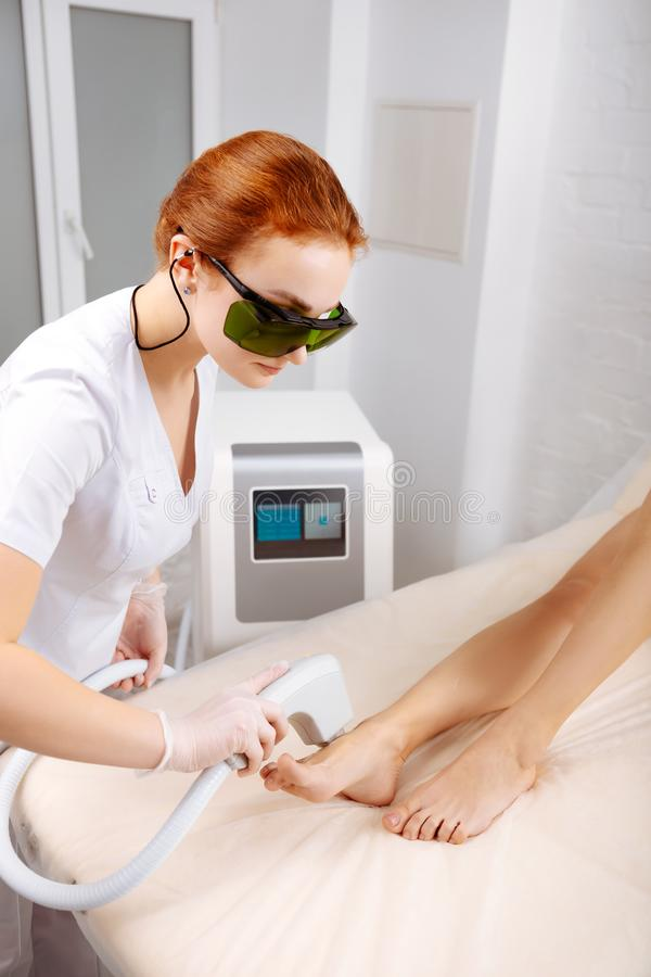 Professional Depilation Master Removing Unwanted Hair From Legs Stock Photo
