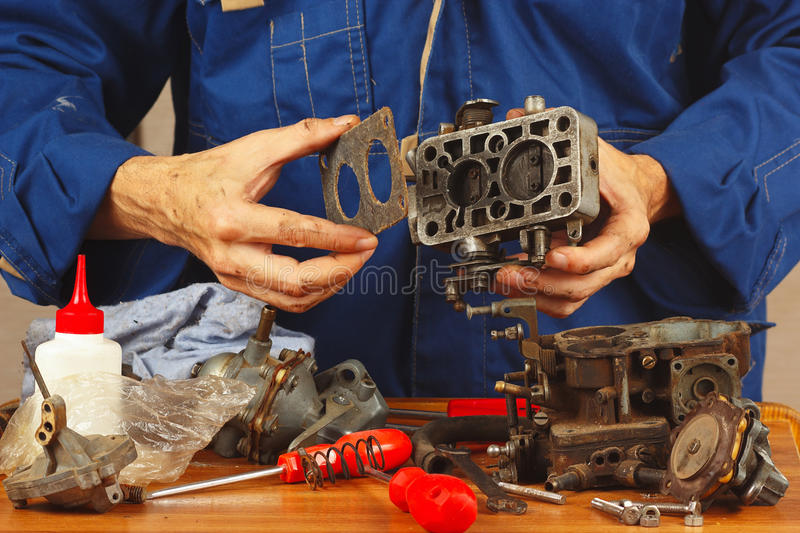 Master repairing parts of automotive engine in workshop royalty free stock photos