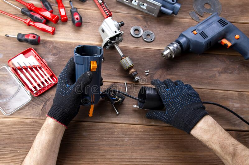 The master repairs a broken electrical device: drill, cutter on a wooden table. Electric Tool Repair Shop royalty free stock image