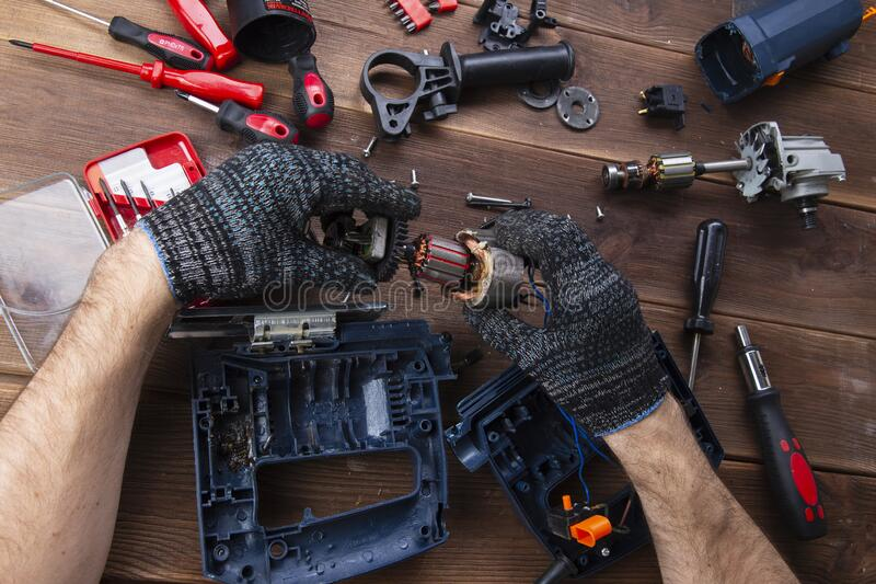 The master repairs a broken electrical device: drill, cutter on a wooden table. Electric Tool Repair Shop stock image