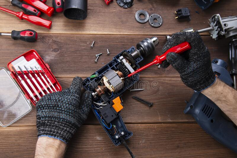 The master repairs a broken electrical device: drill, cutter on a wooden table. Electric Tool Repair Shop royalty free stock images