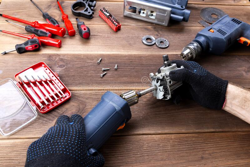 The master repairs a broken electrical device: drill, cutter on a wooden table. Electric Tool Repair Shop stock photo