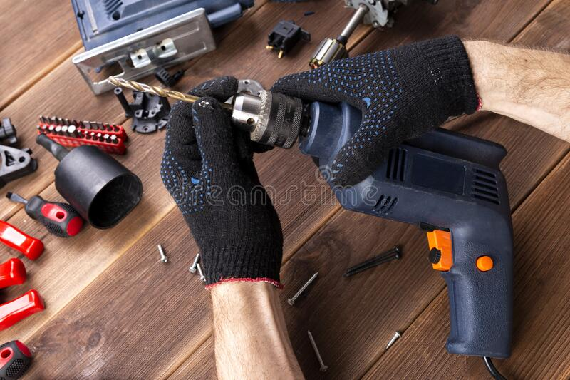 The master repairs a broken electrical device: drill, cutter on a wooden table. Electric Tool Repair Shop royalty free stock photo