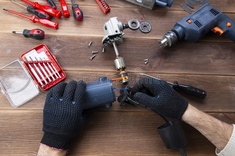 The master repairs a broken electrical device: drill, cutter on a wooden table. Electric Tool Repair Shop royalty free stock photography