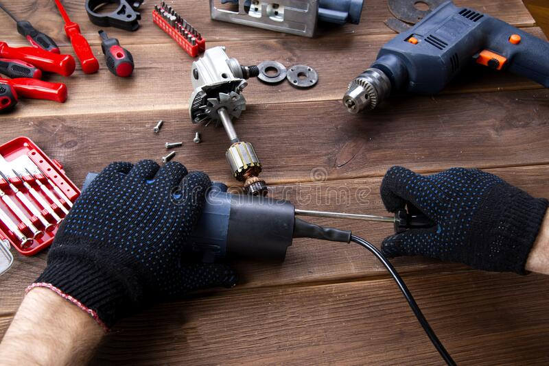 The master repairs a broken electrical device: drill, cutter on a wooden table. Electric Tool Repair Shop royalty free stock photos