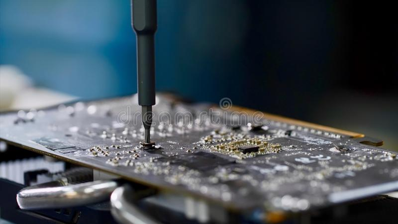 PC technician screws chipset of graphics card to ventilator installing it. Master repairs of computer equipment, establishing chip and circuits. PC technician royalty free stock photography