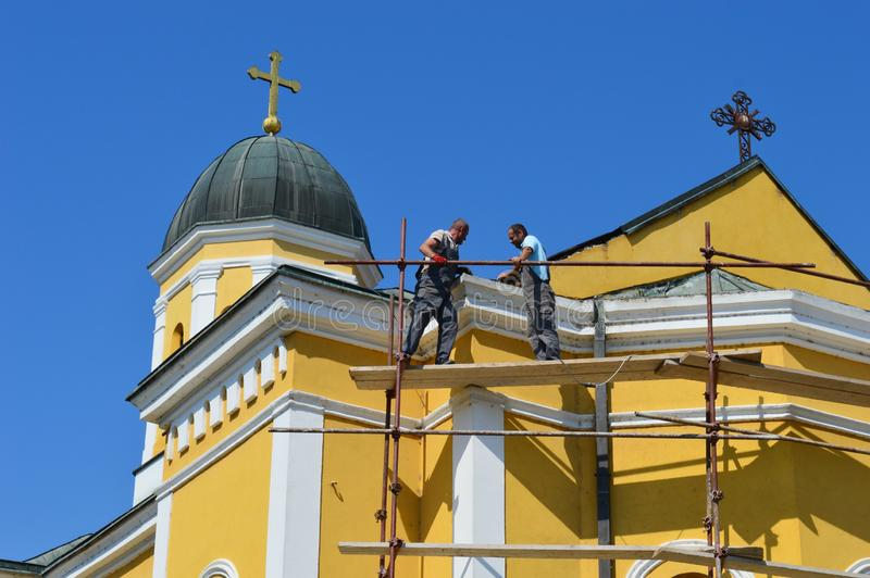 master repairs the roof of the church stock photos
