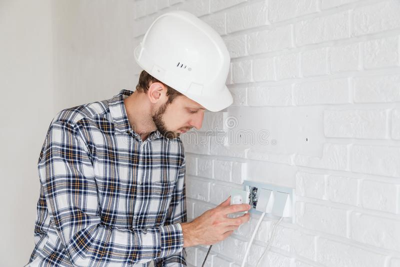 The master repairs the socket with a screwdriver installing it into the wall royalty free stock photography