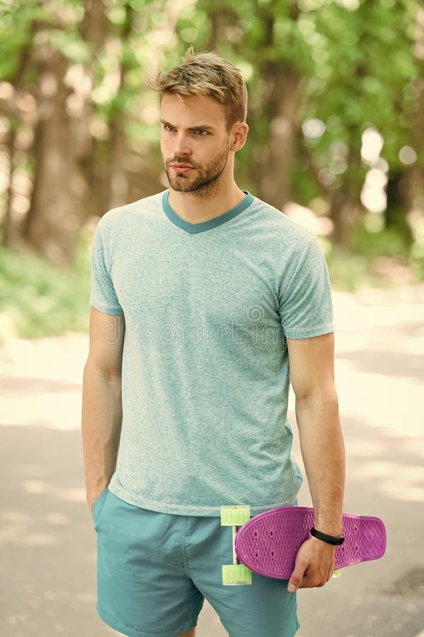 He is master of skateboard tricks. Guy carries penny board ready to ride. Man serious face carries penny board park royalty free stock photography