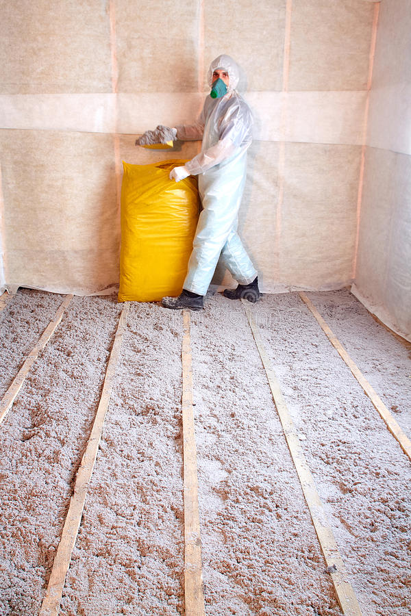 Master stacked cellulose insulation in the floor. Insulated floor, a warm home, eco-friendly insulation, insulation paper, builder at work royalty free stock images