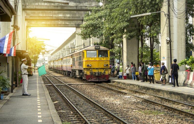 Master Station is waving green flag to make signaling for Make train depart leave. BANGKOK, THAILAND - 27 Jan 2018 : Master is waving green flag to make stock photos
