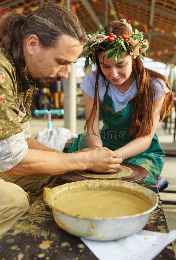 Master teaches a girl in a flower wreath pottery. Master class at the festival of young wine in the Valley of Lefkadia royalty free stock images