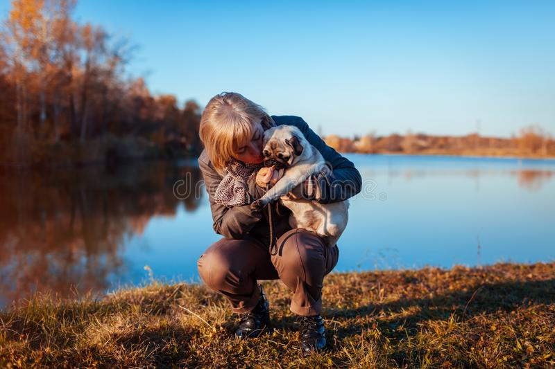 Master walking pug dog in autumn park by river. Happy woman hugging and feeding pet. royalty free stock photo