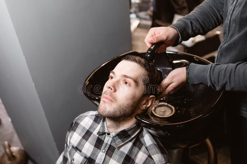 Master washes the head of the client in the Barber shop, hairdresser makes hairstyle for a young man. royalty free stock image