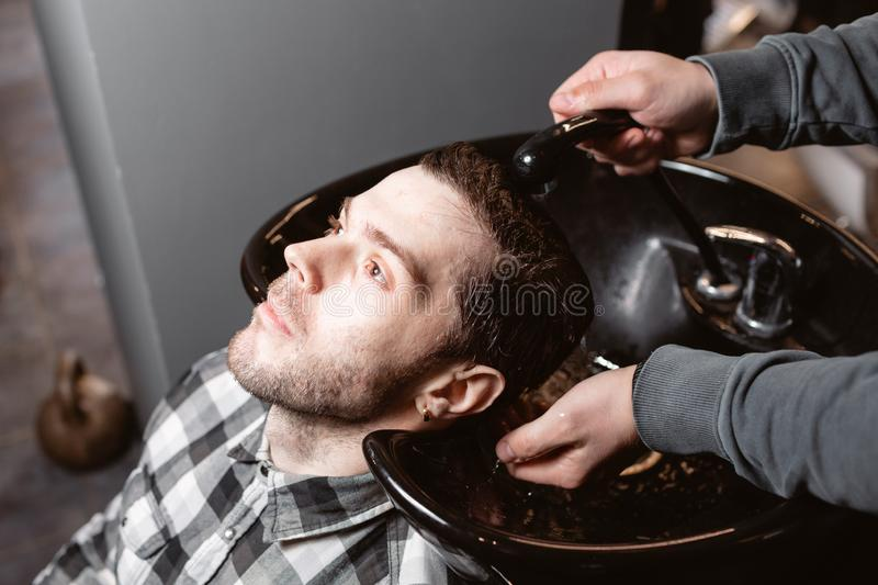 Master washes the head of the client in the Barber shop, hairdresser makes hairstyle for a young man. Master washes the head of the client in the Barber shop stock image