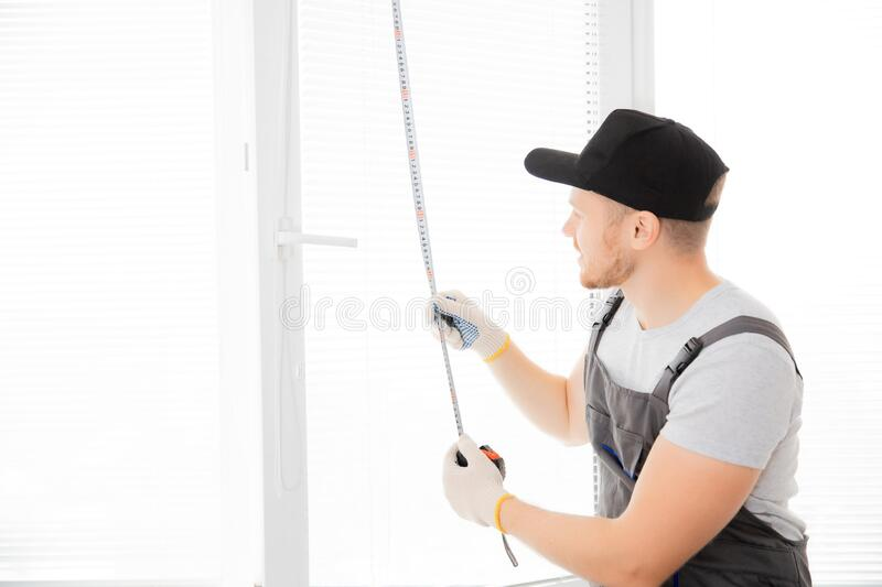 Master worker measures upvc window with ruler, installation process royalty free stock photography