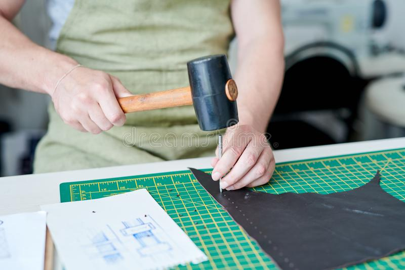 Master working with leather. Close-up of male master working with hammer and piece of leather at the table royalty free stock photos
