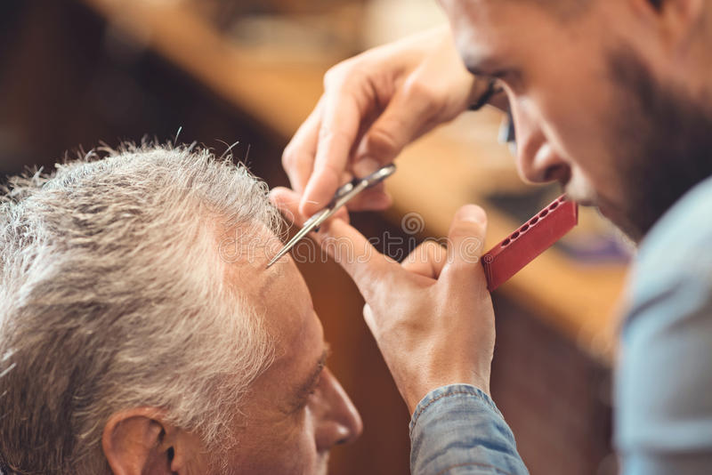 Masterful barber making hairdo of the retired client in barbershop. Designing new haircut. Involved charming young master standing in the barbershop and cutting stock photography