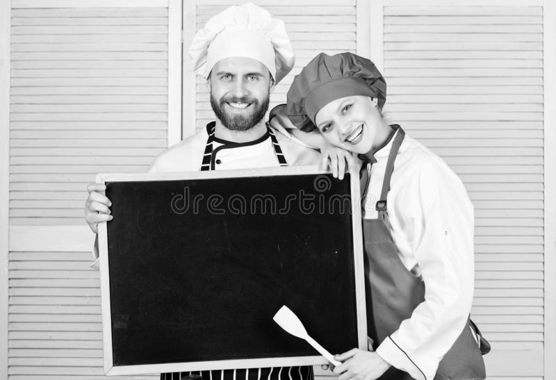 Mastering cooking skills. Couple of man and woman holding empty blackboard in cooking school. Master cook and prep cook stock photos