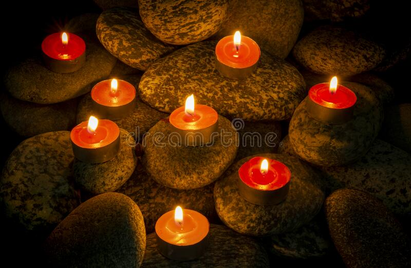 Masterizzazione Composizione delle candele sui sassi sullo sfondo immagine stock