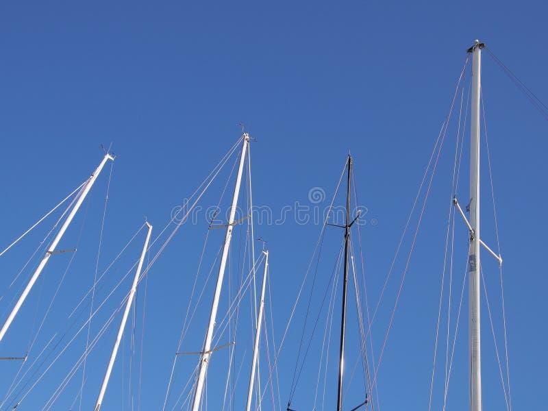 Mastros do veleiro contra o céu azul foto de stock