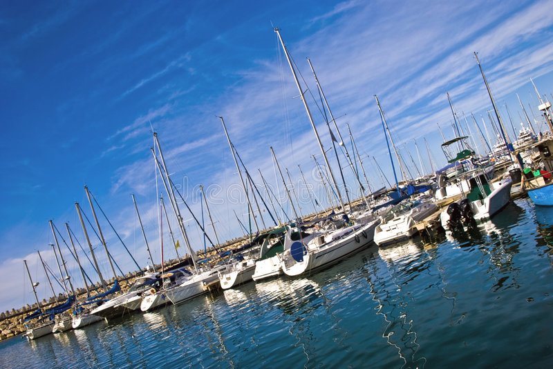 Masts. Of modern sailboats against the cloudy blue sky background royalty free stock photography