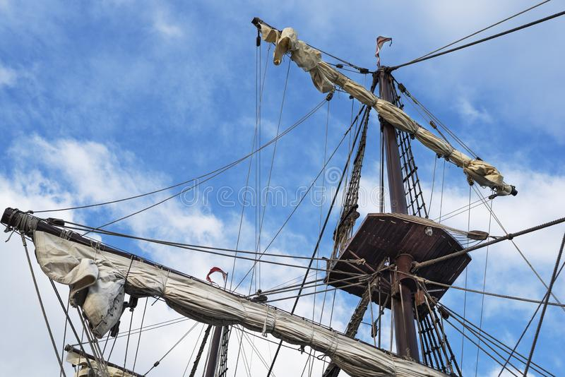 Masts and rigging of old pirate ship on background of cloudy blue sky. Masts and rigging of an old pirate ship on background of cloudy blue sky royalty free stock photo