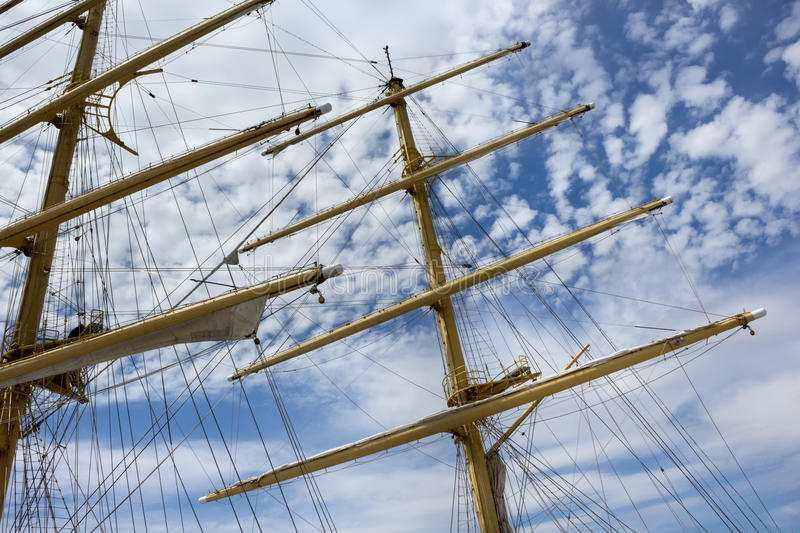 Masts and rigging of a sailing ship. Against blue sky and beautiful clouds stock photo