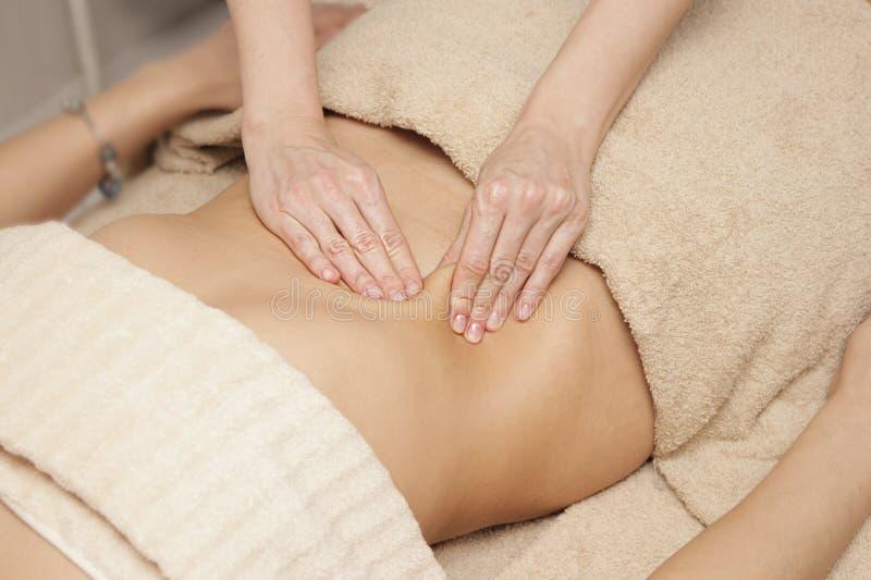 Masuje terapeuty robi leczniczemu masażowi podbrzusze dla kobiety obraz stock