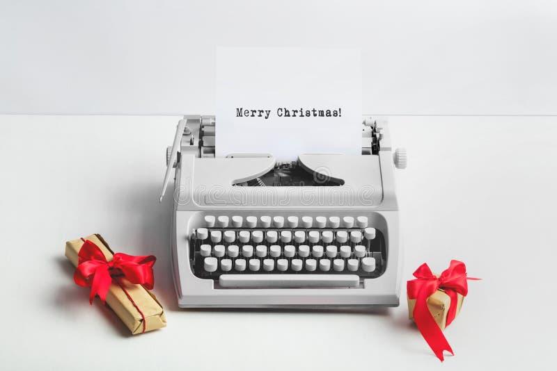 Maszyna do pisania z WESOŁO bożymi narodzeniami tekst i prezenty obrazy stock