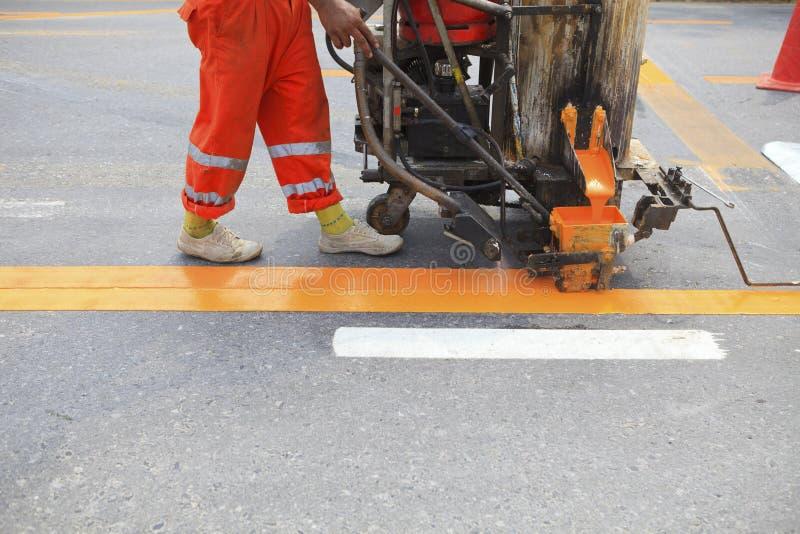 Maszyna i pracownik przy budową drogi zdjęcie stock