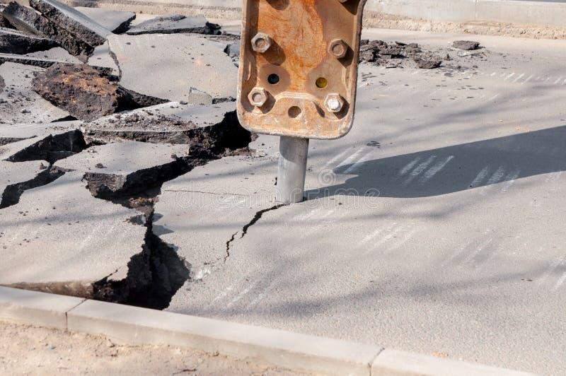 maszyna musztruje asfalt Wielcy czerepy ziemia wsz?dzie i jamy na drodze pracuj?cy wyposa?enie z ?widerem pracuje g?o?no obraz stock
