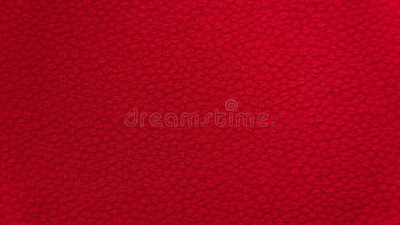 Matérias têxteis vermelhas da tela do fundo com um teste padrão pequeno do bordado fotografia de stock royalty free