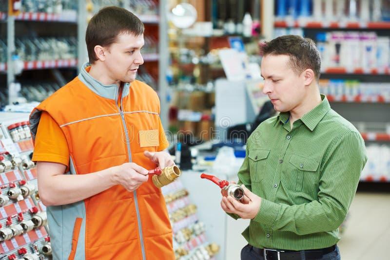 Matériel d'achats homme de aide auxiliaire choisissant la valve images stock