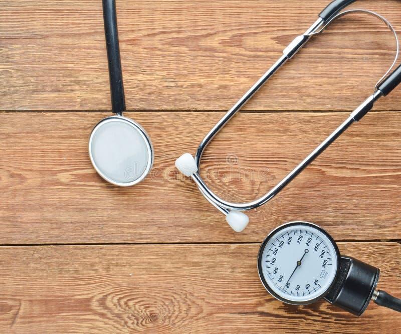 Matériel médical cardiologique pour mesurer la pression sur une table en bois Stéthoscope et mètre de mesure image libre de droits