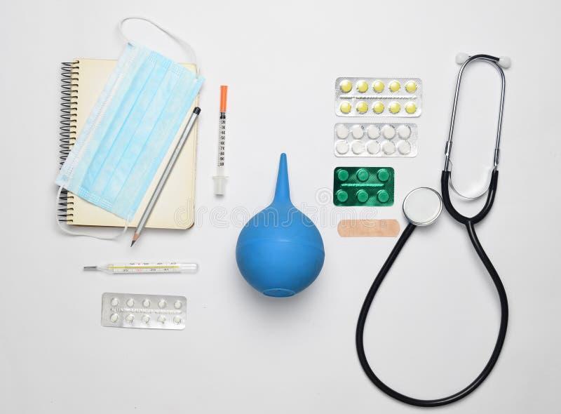 Matériel médical sur un fond blanc Stéthoscope, comprimé, thermomètre, carnet, seringue, lavement Concept médical, vue supérieure images libres de droits