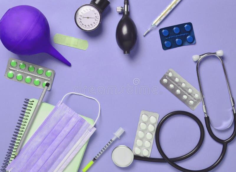 Matériel médical sur un fond bleu Lavement, pilules de boursouflures, n photos stock