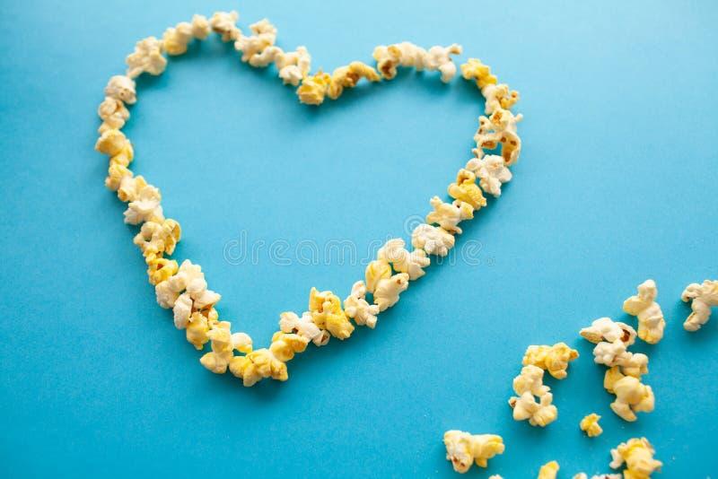 Mat Bild av hjärtaformerna från popcorn Läckert popcorn på blå bakgrund bio fotografering för bildbyråer