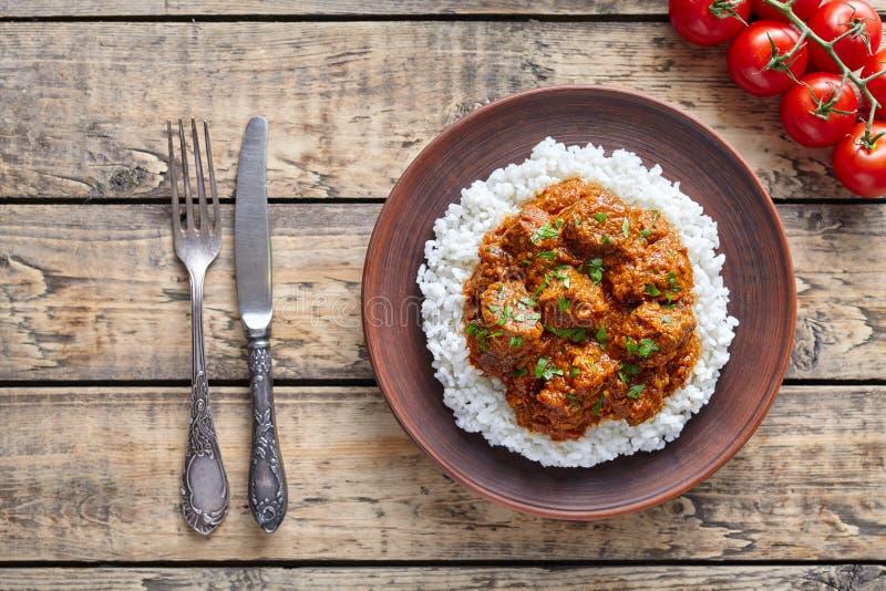 Mat för lamm för kock för traditionell sås för Madras smörnötkött kryddig långsam med ris och tomater i leramaträtt arkivfoto