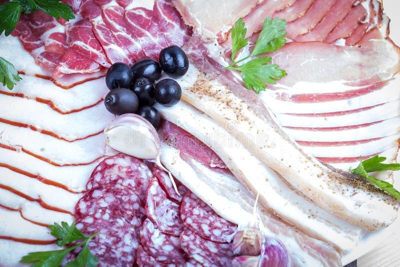 Mat för mellanmål för platta för kallt kött italiensk med skinka, prosciuttoen, salami, griskött och korven i en platta på träbak royaltyfria foton
