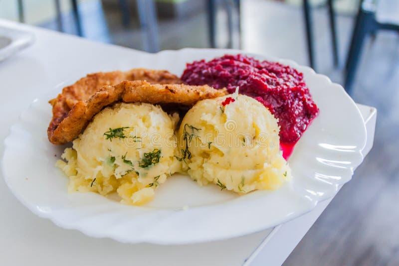 Mat i Polen - bröad feg filet, mosade potatisar och bi royaltyfri foto