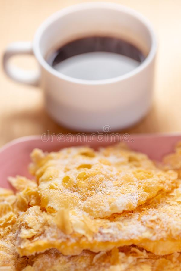 Mat och efterr?tt Knastrade frasiga kakor med socker p? en platta och en kopp kaffe p? en tr?tabell royaltyfria bilder